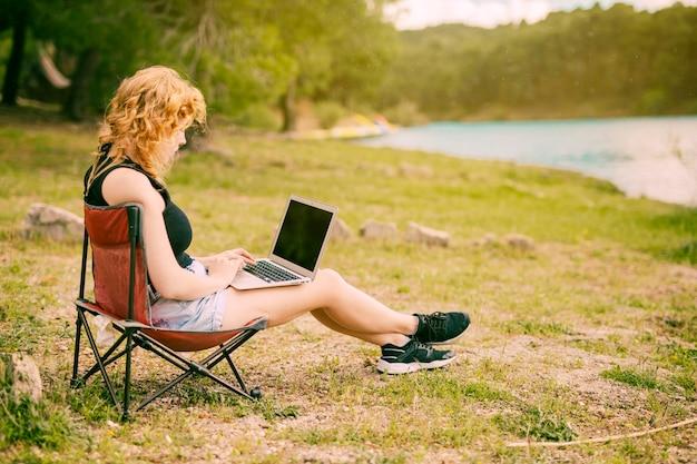 Jeune femme à l'aide d'un ordinateur portable à l'extérieur Photo gratuit