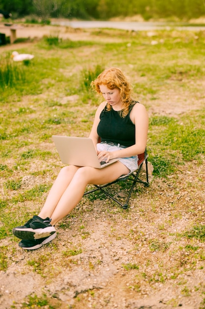 Jeune femme à l'aide d'un ordinateur portable en forêt Photo gratuit