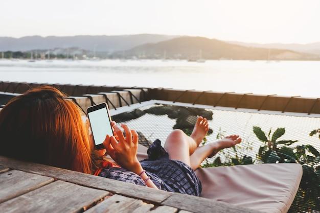 Jeune femme à l'aide de smartphone avec écran blanc tout en se trouvant côté mer avec coucher de soleil du soir. Photo Premium