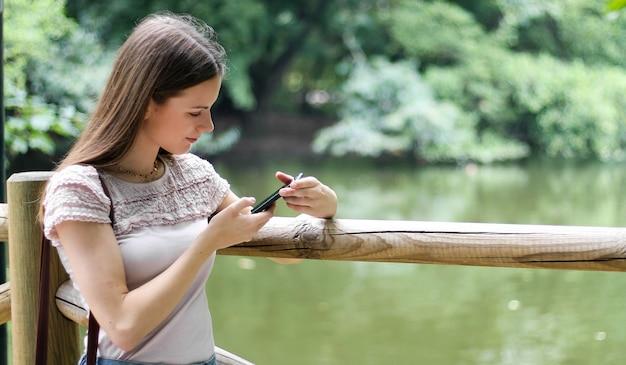 Jeune femme à l'aide de son smartphone dans un parc Photo Premium
