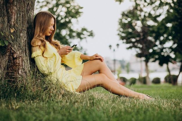 Jeune Femme à L'aide De Téléphone Et Assis Sous L'arbre Dans Le Parc Photo gratuit