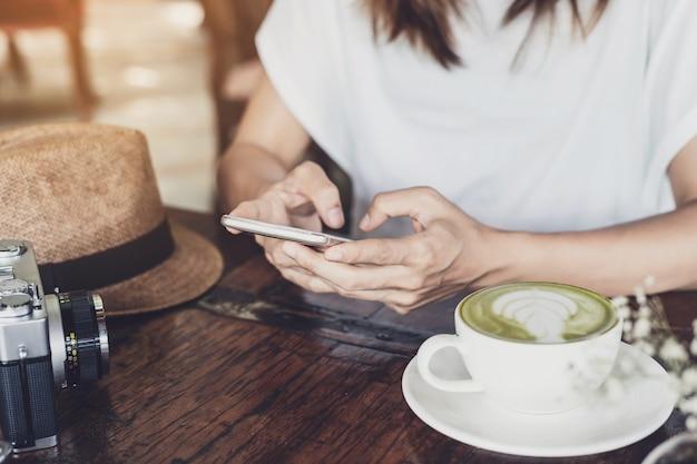 Jeune femme à l'aide de téléphone intelligent et de boire du café au café Photo Premium