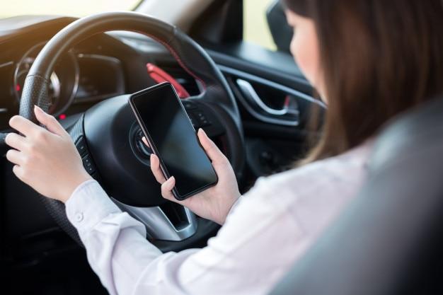 Jeune femme à l'aide de téléphone intelligent en conduisant une voiture Photo Premium