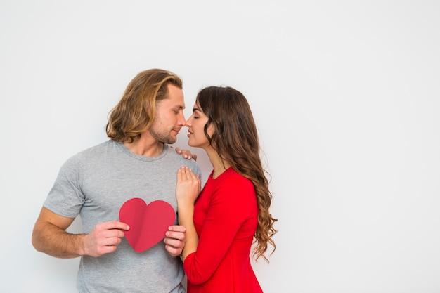Jeune femme aimant son copain tenant du papier de forme de coeur dans la main sur fond blanc Photo gratuit