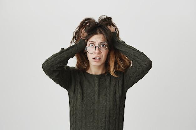 Jeune Femme Alarmée à Lunettes, Panique Et ébouriffe Les Cheveux Photo gratuit