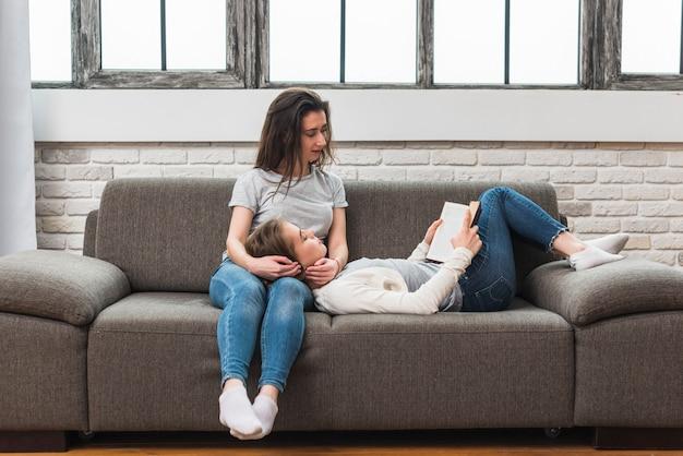 Jeune Femme Allongée Sur Les Genoux De Sa Copine En Lisant Le Livre Sur Un Canapé Photo gratuit
