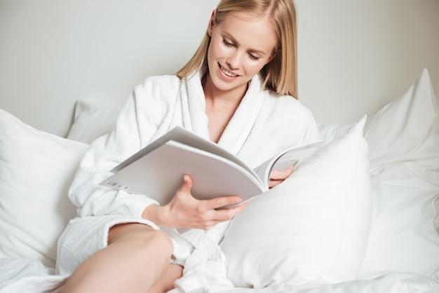 Jeune Femme Allongée Sur Le Lit Dans La Chambre D'hôtel Photo gratuit