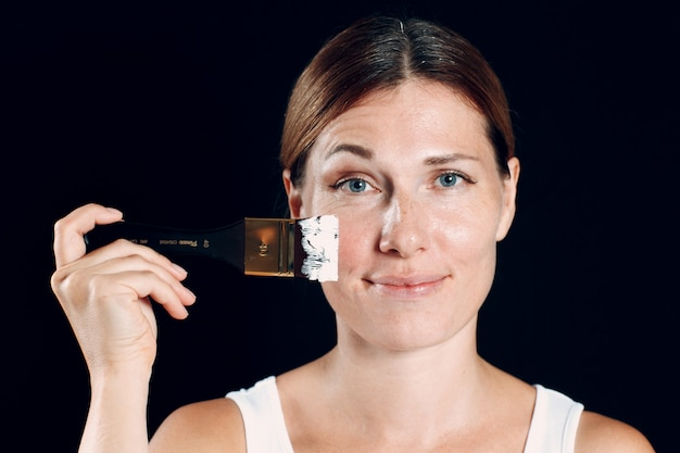 Jeune Femme Appliquant Le Maquillage, Peint Le Visage Avec Le Pinceau Et Le Maquillage. Comment Ne Pas Faire De Concept De Maquillage. Photo Premium