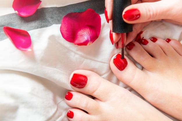 Jeune femme applique un vernis rouge sur les orteils Photo Premium