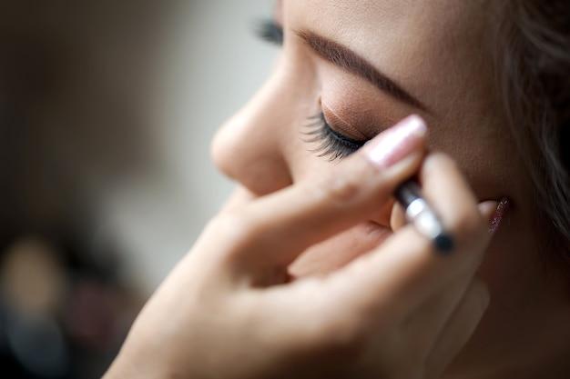 Jeune femme appliquée eyeliner. Photo Premium