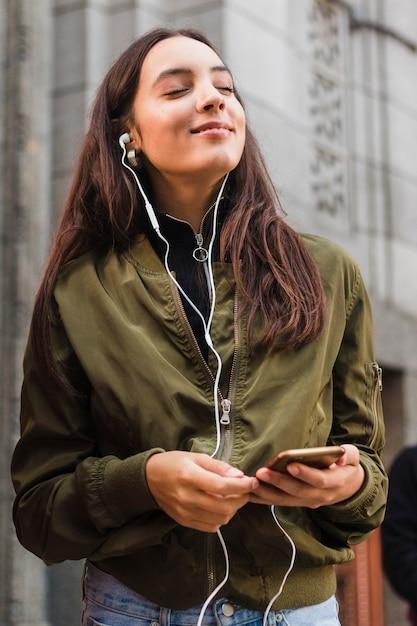 Jeune femme appréciant la musique sur des écouteurs à l'aide d'un téléphone portable Photo gratuit