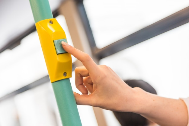 Jeune femme en appuyant sur le bouton de demande d'arrêt dans le bus Photo Premium