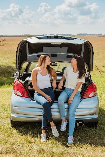 Jeune femme appuyée contre leur voiture Photo gratuit