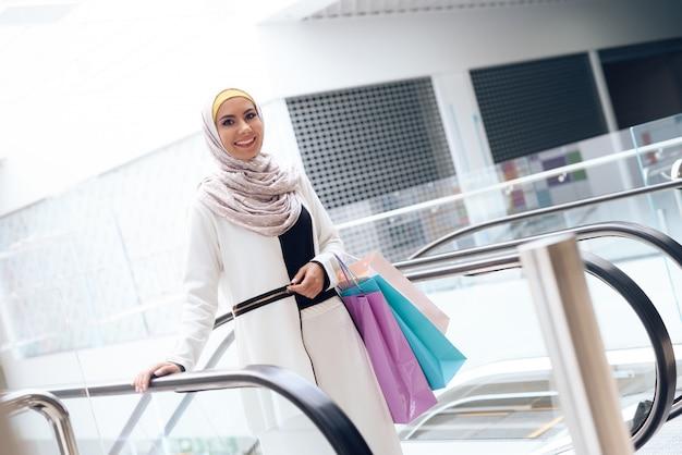 Jeune femme arabe avec des colis debout dans le centre commercial Photo Premium