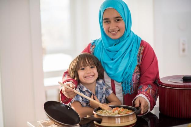 Jeune femme arabe avec petit enfant dans la cuisine Photo Premium
