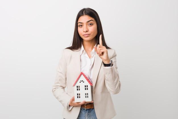 Jeune Femme Arabe Tenant Une Icône De La Maison Montrant Le Numéro Un Avec Le Doigt. Photo Premium