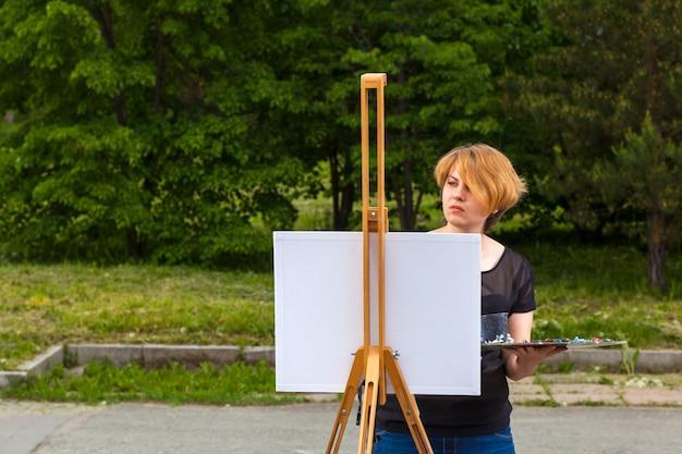 Jeune femme artiste peint sur une toile un paysage urbain Photo Premium