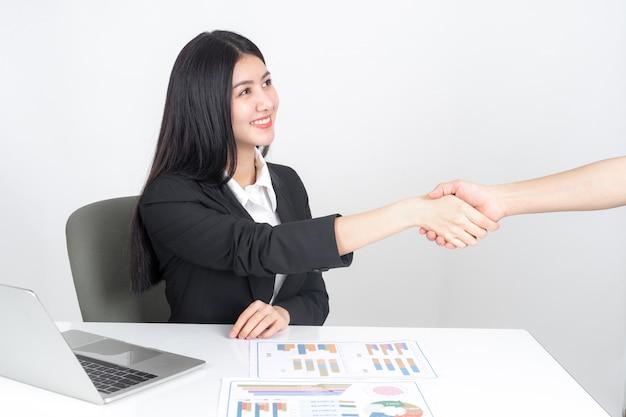 Jeune femme asiatique à l'aide d'un ordinateur portable sur le bureau Photo gratuit