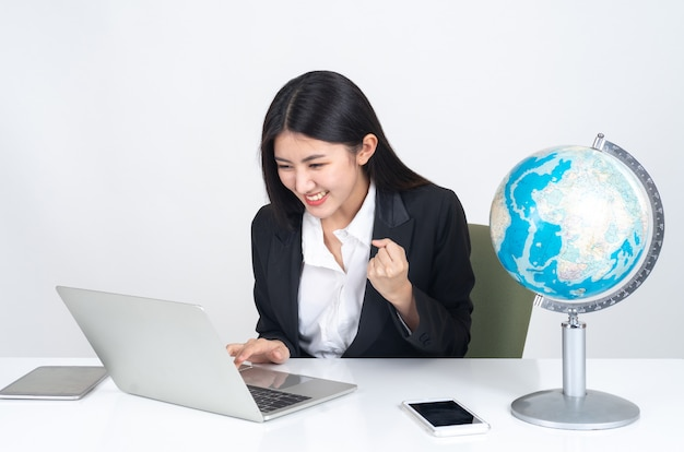 Jeune femme asiatique à l'aide d'un ordinateur portable et d'un téléphone intelligent sur le bureau Photo gratuit