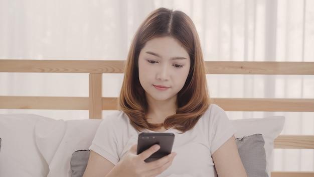 Jeune femme asiatique à l'aide de smartphone en position couchée sur le lit après le réveil du matin Photo gratuit