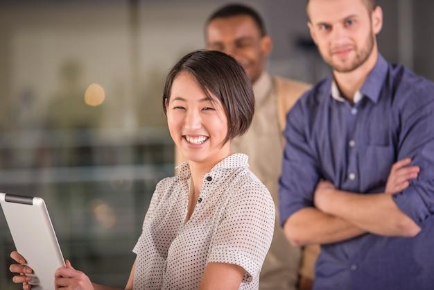 Jeune femme asiatique à l'aide de tablette et souriant Photo Premium