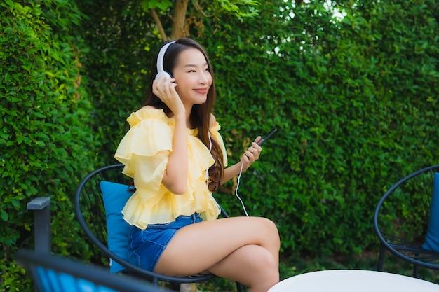 Jeune Femme Asiatique à L'aide D'un Téléphone Mobile Intelligent Avec Un Casque Pour écouter De La Musique Autour D'un Jardin Extérieur Photo gratuit