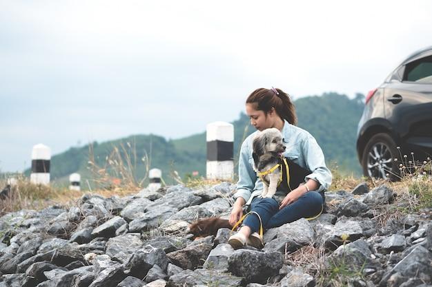 Jeune femme asiatique assis avec ses chiens à côté de la route avec la voiture noire et la borne kilométrique. Photo Premium