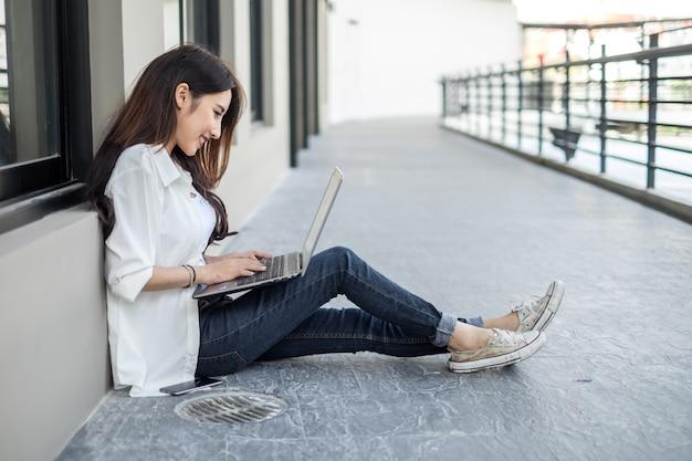 Jeune femme asiatique assise dans la rue et travaillant avec son ordinateur portable tout en parlant au téléphone mobile Photo Premium