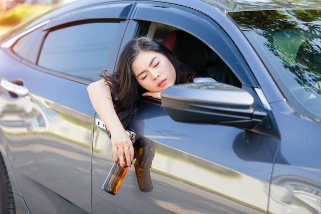 Jeune femme asiatique buvant de la bière en conduisant une voiture. Photo Premium