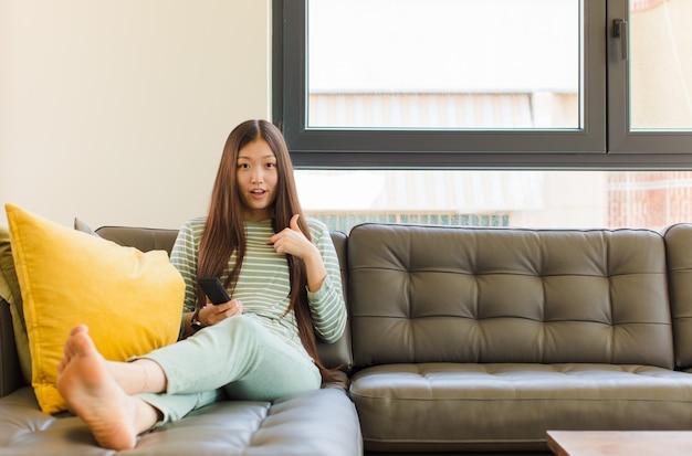 Jeune Femme Asiatique à La Choqué Et Surpris Avec La Bouche Grande Ouverte, Pointant Vers Soi Photo Premium