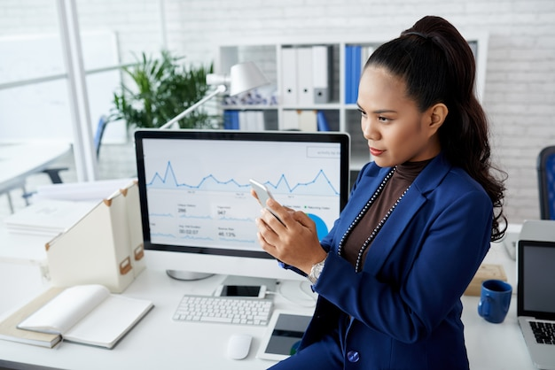 Jeune femme asiatique en costume assis sur un bureau dans le bureau et à l'aide de smartphone Photo gratuit