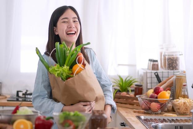 Jeune femme asiatique dans la cuisine et la tenue de sac d'épicerie Photo Premium