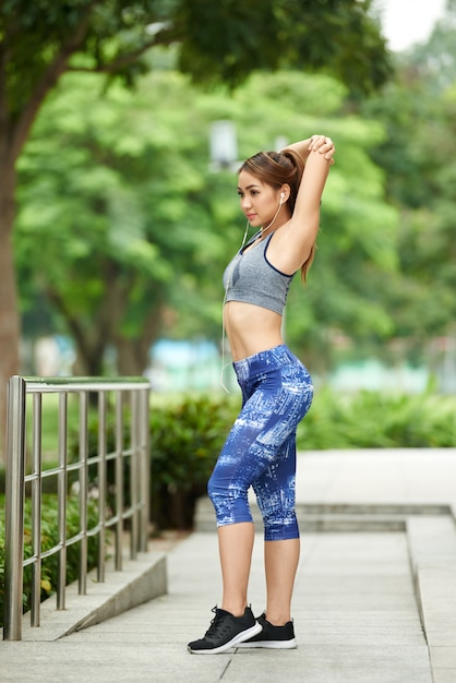 Jeune, femme asiatique, dans, sport, sommet, et, leggings, faire, étirer bras, dans parc Photo gratuit