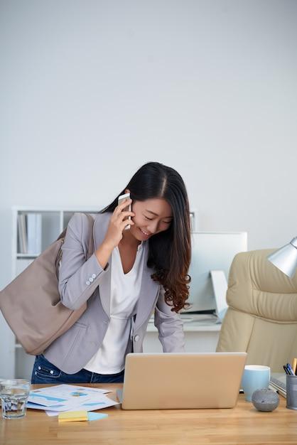 Jeune femme asiatique debout au bureau, utilisant un ordinateur portable et parlant au téléphone Photo gratuit