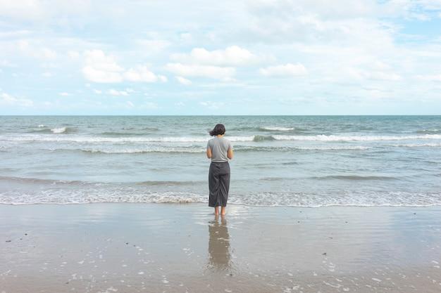 Jeune femme asiatique debout face à la mer. se sentir vraiment seul, mer déchirée comme Photo Premium