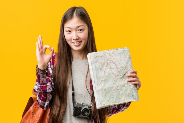 Jeune femme asiatique détenant une carte joyeuse et confiante, montrant le geste correct. Photo Premium