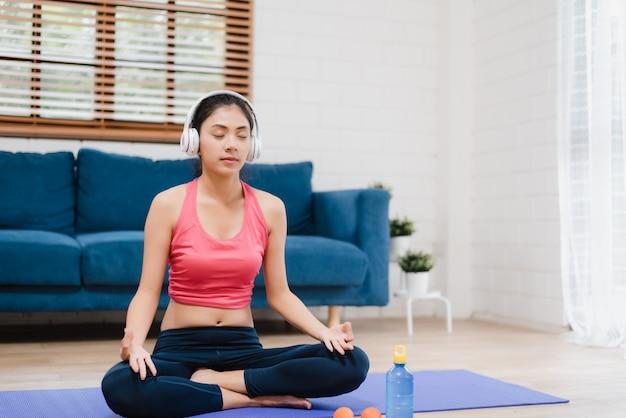 Jeune femme asiatique écoute de la musique tout en pratiquant le yoga dans le salon Photo gratuit