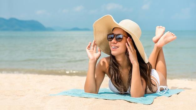 Jeune femme asiatique heureuse avec chapeau de soleil se trouvant à la plage en été Photo Premium