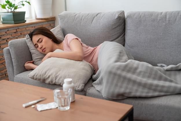 Jeune femme asiatique malade relaxant et dormir sur le canapé avec oreiller après avoir pris des médicaments avec un verre d'eau Photo Premium