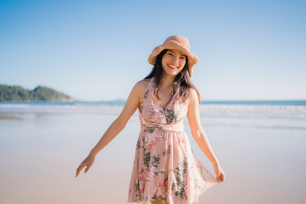 Jeune femme asiatique marchant sur la plage. belle femme heureuse se détendre à pied sur la plage Photo gratuit