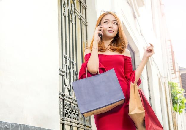 Jeune femme asiatique parlant sur téléphone mobile tout en portant des sacs Photo Premium