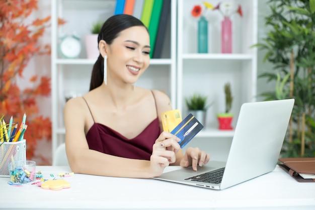 Jeune femme asiatique payant avec carte de crédit Photo gratuit