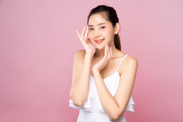 Jeune femme asiatique avec une peau blanche fraîche et propre, toucher doucement son propre visage dans une pose de beauté Photo Premium