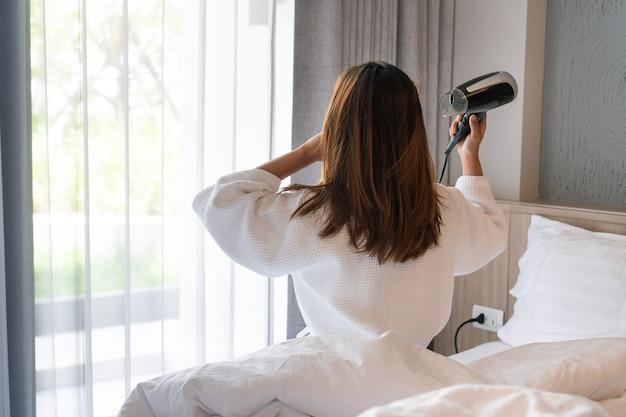Jeune Femme Asiatique En Peignoir Blanc Assis Sur Son Lit Et Séchant Ses Cheveux Le Matin Photo Premium
