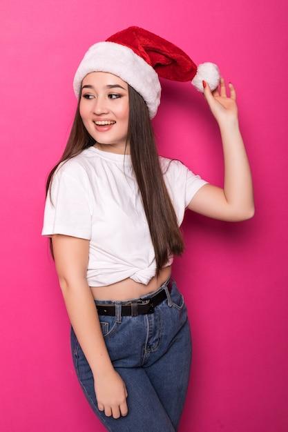 Jeune Femme Asiatique Portant Le Chapeau Du Père Noël Isolé Sur Un Mur Rose Photo gratuit