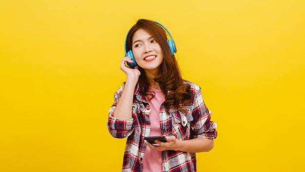 Jeune Femme Asiatique Portant Des écouteurs Sans Fil, écoutant De La Musique De Smartphone Avec Une Expression Joyeuse Dans Des Vêtements Décontractés Et Regardant La Caméra Sur Le Mur Jaune. Concept D'expression Faciale. Photo gratuit