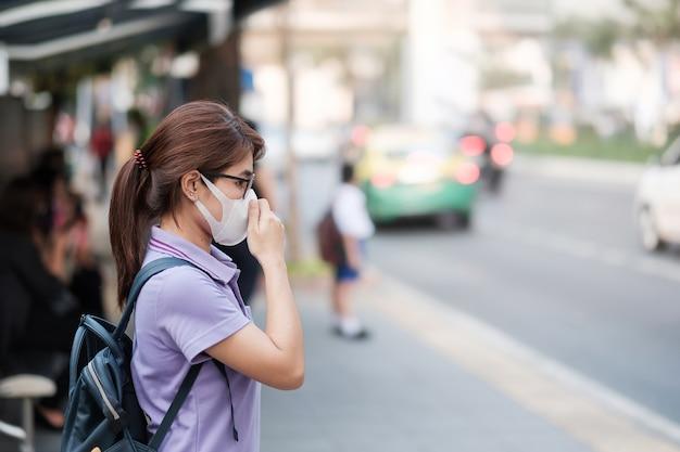 Une Jeune Femme Asiatique Portant Un Masque Respiratoire N95 Protège Et Filtre Les Pm2,5 (particules) Contre La Circulation Et La Poussière En Ville. Concept De Santé Et De Pollution De L'air Photo Premium