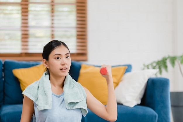 Jeune femme asiatique pratiquant le yoga dans le salon. Photo gratuit