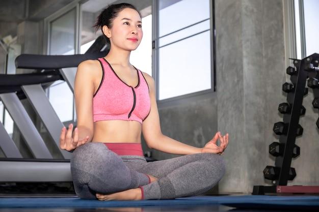 Jeune femme asiatique pratiquant le yoga sur un gymnase Photo Premium