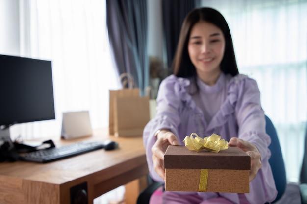 Jeune femme asiatique reçoit une boîte cadeau en une journée spéciale. Photo Premium